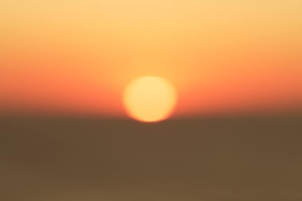 A hot sun glowing red and orange in the distance