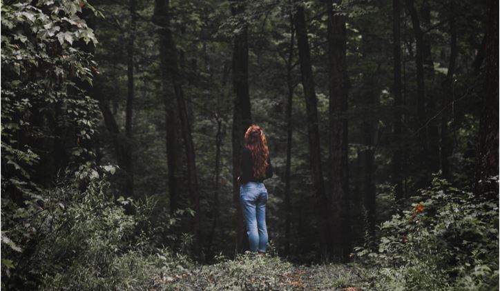 Woman standing viewing a forest